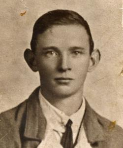 Posed sepia photograph, head and shoulders of James Nolan prior to enlisting aged 20. Freshfaced, short dark hair, wearing a white shirt with narrow knotted tie and a lighted coloured relaxed jacket.